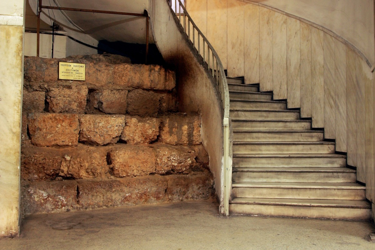 Άποψη του κλιμακοστασίου του υπογείου επί της Δραγατσανίου 6, όπου διακρίνεται το διατηρημένο τμήμα του αρχαίου τείχους (Α.-Μ. Θεοχαράκη 2015. Τα αρχαία τείχη των Αθηνών. Ελληνική Επιγραφική Εταιρεία: 317).